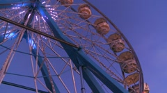 A ferris wheel spins and is brightly lit. - stock footage