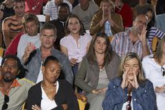 Annoyed People in Auditorium Seats - stock photo
