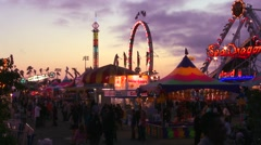 A shot at dusk of a carnival, amusement park or state fair. - stock footage