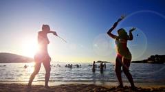 Silhouette girls play beach leisure tennis game. Stock Footage