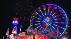 Fireworks explode in the night sky behind a ferris wheel at a carnival or state Stock Footage