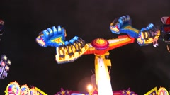 A tilt a whirl type ride at an amusement park or carnival. - stock footage
