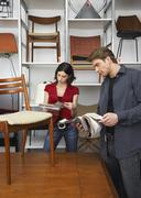 People Looking at Upholstery Samples in Furniture Store - stock photo