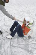 Man Helping Woman Up from Ice Stock Photos