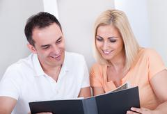 Portrait of happy couple looking at photo album Stock Photos