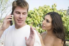 Woman Interrupting Man on Phone - stock photo