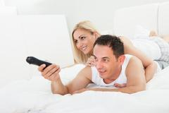 woman lying on man's back watching television - stock photo