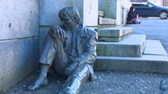 A homeless person sits near a statue depicting a homeless person on the streets Stock Footage