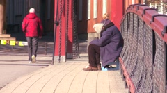 A homeless person sits on a bridge in Norway. - stock footage