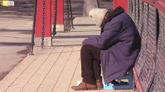A homeless person sits on a bridge in Norway. Stock Footage