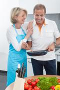 happy mature couple cooking food in kitchen - stock photo