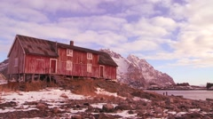 Time lapse of clouds moving behind a weathered red fishing village in the Arctic Stock Footage