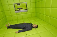 Man Lying on Back in Green Padded Room with Television - stock photo