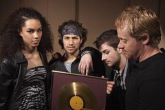 Band Holding Gold Album Stock Photos