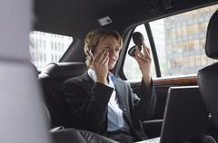 Woman Applying Make-Up in Back Seat of Car Stock Photos