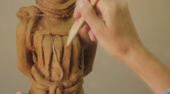 Sculptor Uses Tool To Sculpt Side Of Statue , Clay Stock Footage