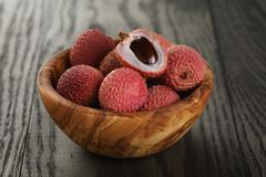 Ripe lychees in wood bowl Stock Photos