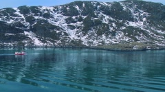A fishing boat heads through fjords in the Arctic on glassy green water in the - stock footage