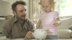 Father helping daughter to save money in piggy bank - stock footage