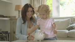 Mother helping daughter to save money in piggy bank Stock Footage