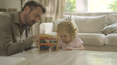 Father assisting his daughter in counting abacus Stock Footage