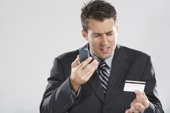 Man with Cellular Phone and Credit Card - stock photo