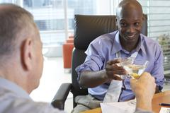 Businessmen Toasting in Office Stock Photos