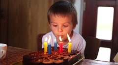 Adorable five year old boy celebrating his birthday and blowing candles Stock Footage