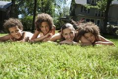 Portrait of Mother and Children Laying on Grass Stock Photos