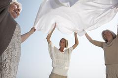 Women Shaking out Sheet Stock Photos