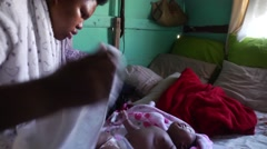 African mother dresses baby in shack,South Africa Stock Footage