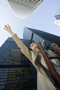 Businesswoman Standing on Ladder Reaching Upwards - stock photo