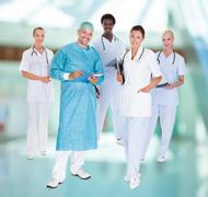 happy doctor in surgical gown with his coworkers - stock photo