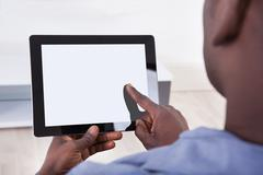 african person sitting with digital tablet - stock photo