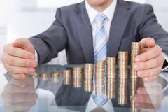 Businessman protect stack of coins Stock Photos