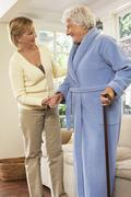 Senior Woman Receiving Assistance with Standing - stock photo