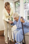 Senior Woman Receiving Assistance with Getting out of Chair - stock photo