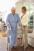 Senior Woman Receiving Assistance with Using Walker - stock photo