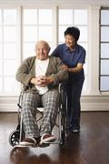 Senior Man Receiving Assistance with Wheelchair Stock Photos
