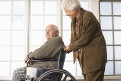 Senior Man Receiving Assistance with Wheelchair - stock photo