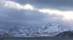 Heavenly light streams down on a beautiful snow covered shoreline amidst fjords Stock Footage