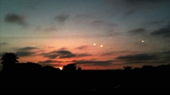 A Fleet of UFOs Over a Sunset Landscape Stock Footage