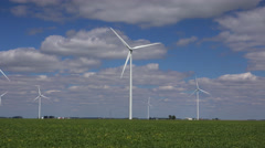 Driving by Windmill turbines  in agricultural field Stock Footage