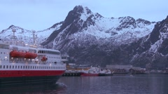 The cruise ship Hurtigruten sails through the fjords of Norway to arrive at - stock footage