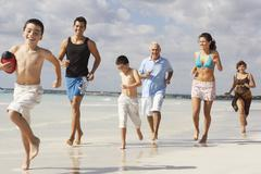 Family Playing Football on the Beach - stock photo