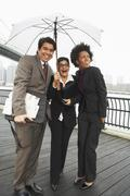 Business People Under Umbrella by East River, New York City, New York, USA - stock photo