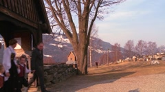 People in traditional clothing walk towards an old wooden stave church in Stock Footage