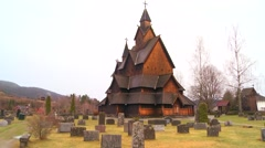 Wide shot of a cemetery in front of an old wooden stave church in Norway. Stock Footage