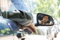 young man reflection on car side mirror - stock photo