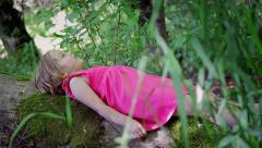 Side View Of A Child Laying On A Log In The Forest, She Is Looking Up Peacefully Stock Footage
